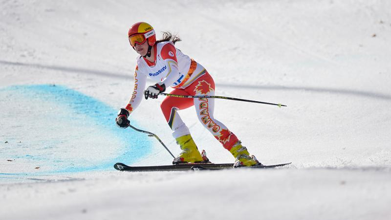 Skier in orange and white ski suit, skis at speed down slope