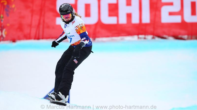 Snowboarder Nicole Roundy rides down course with Sochi 2014 banner in background