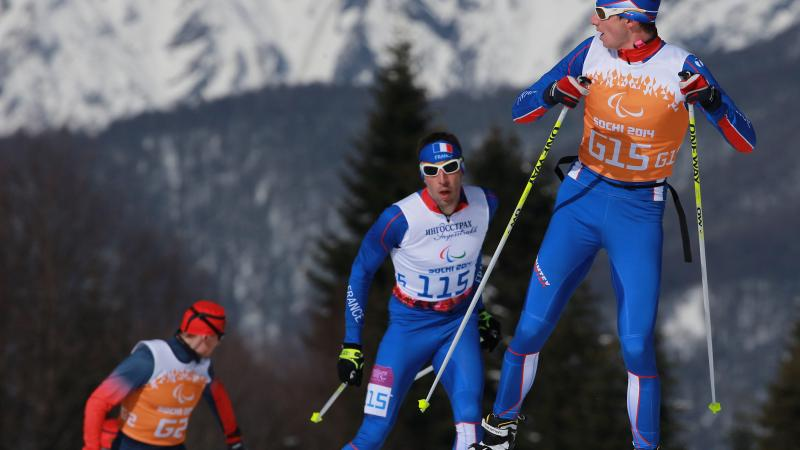 A Nordic skier looks behind him at two other skiers approaching the crest of the hill, close behind him. Mountains are in the background.