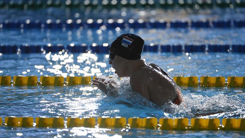 Women with black swim cap swimming breast stroke. Her head is out of the water as she is taking a breath