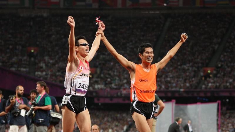 Runner with a guide crossing the finish line with their hands in the air