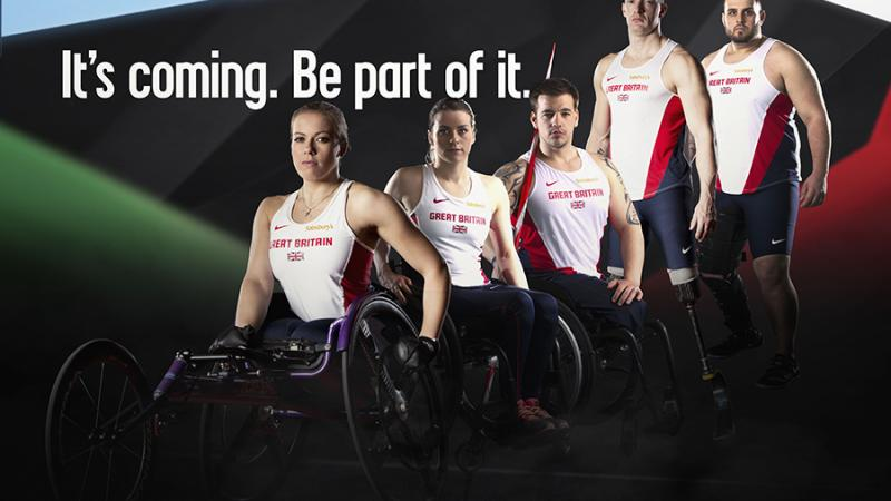5 male and female athletes in British jerseys stand and sit (in wheelchairs) next to each others in front of a black wall. Behind them is the logo: Swansea 2014. It's coming. Be part of it.