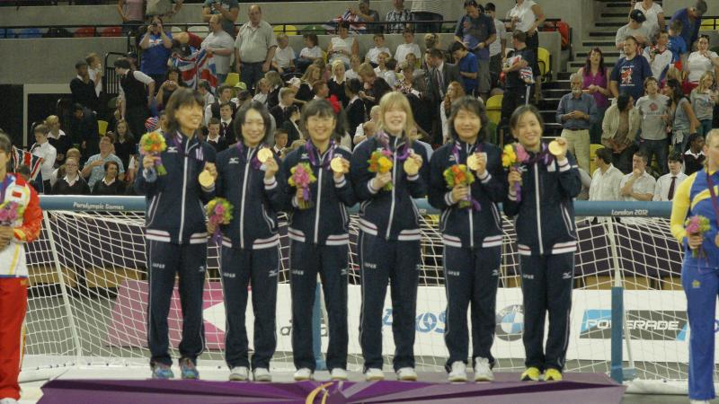 Six women in training suits on podium with medals and flower boquets.