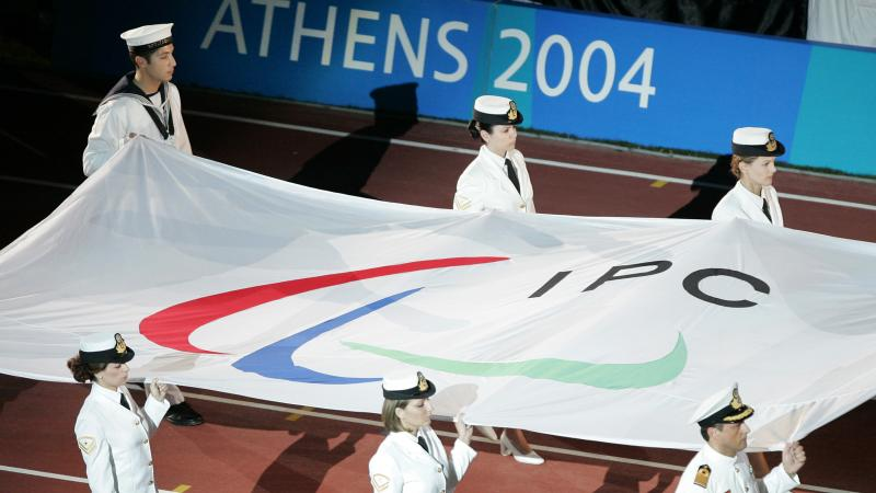 Six people carry a flag with the Paralympic symbol into a stadium