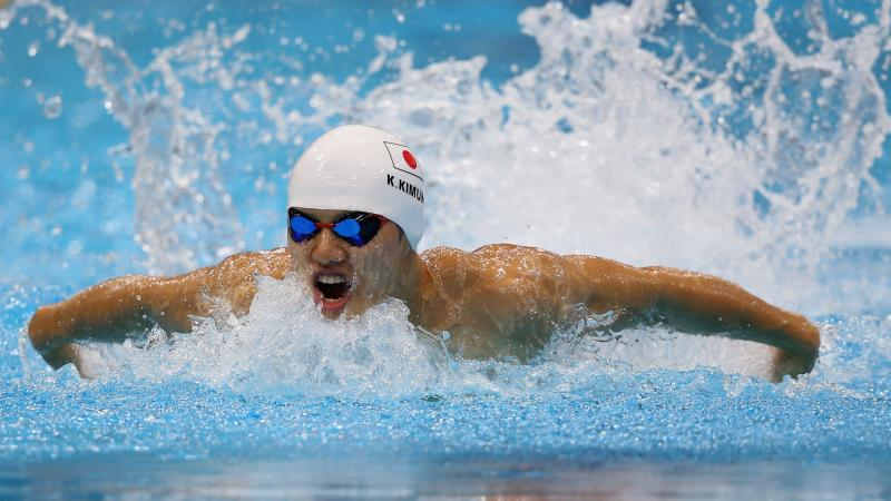 Swimmer in butterfly style in a pool with a simming cap