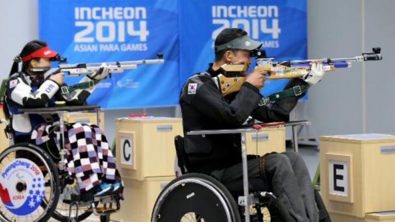 Two people in a shooting range, sitting in wheelchairs and targetting