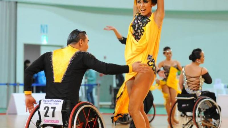 Man in wheelchair and women in dancing costumes doing an emotional latin dance move on the dance floor