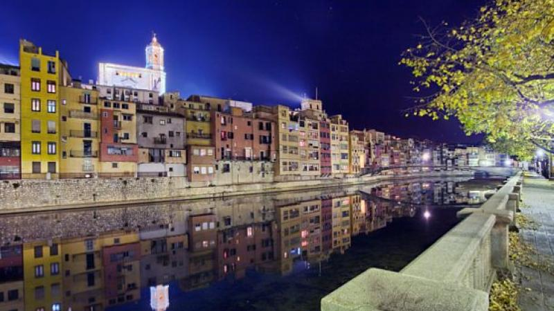 A night time shot of a river bank with stunning buildings in the background.