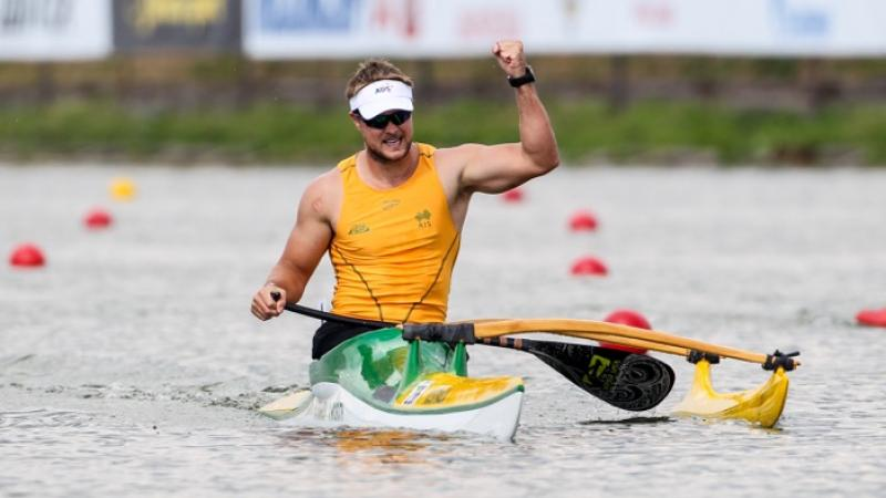 Man in canoe in triumphant pose