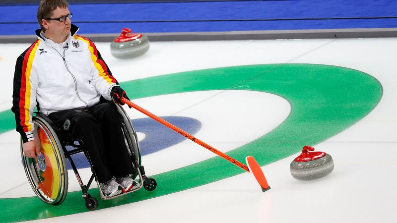 Man in wheelchair on the ice, pointing on a point on the ice