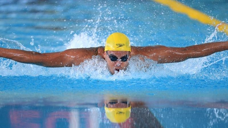 Man with yellow sim cap swimming butterfly