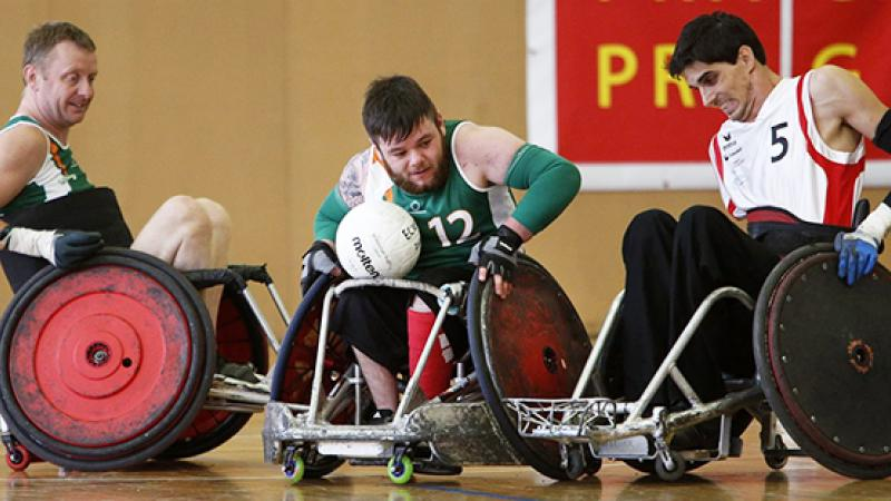 A group of male wheelchair rugby players battling for the ball