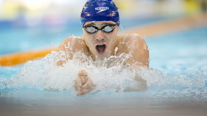 Swimmer with blue swim cap doing breaststroke