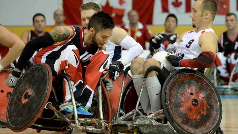 Two wheelchair rugby players tackeling each other