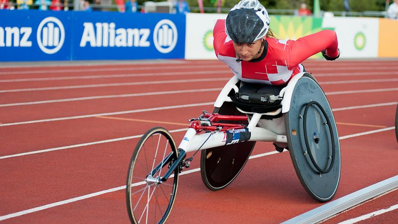 Woman in racing wheelchair competing on the track