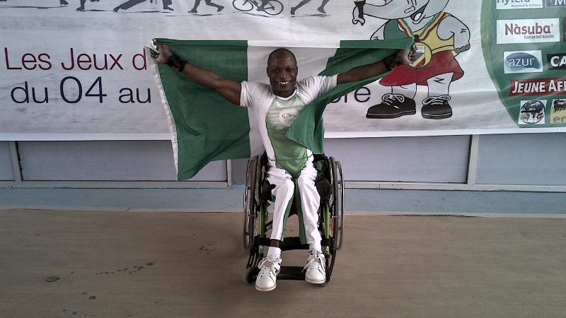 Man in a wheelchair, holding a Nigerian flag and celebrating