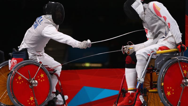 Ruyi Ye (L) of China on his way to winning gold against Yijun Chen (R) of China during the men's individual foil category A final of the wheelchair fencing at the London 2012 Paralympic Games.
