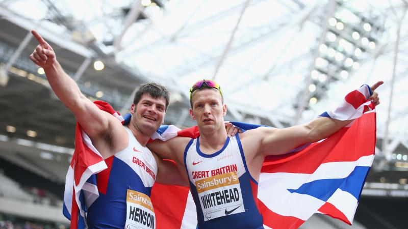 Two men in British racing vests hold a union jack behind them as they celebrate victory,