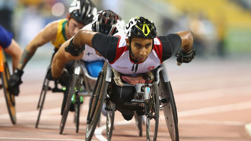 Man leading a pack in a wheelchair race