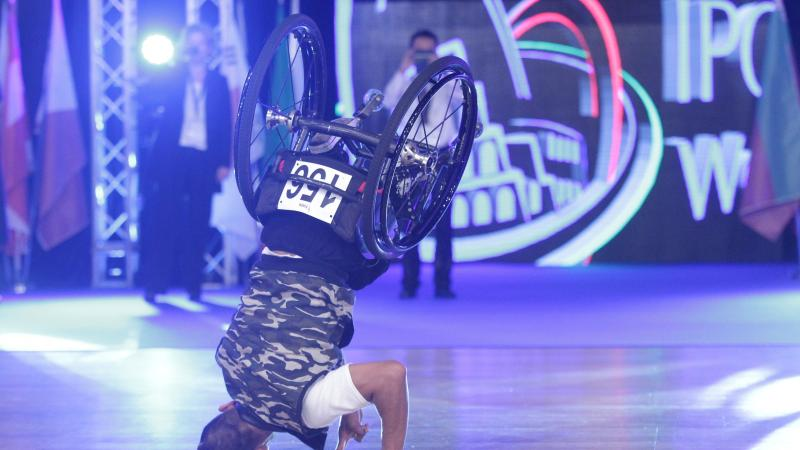 Man in wheelchair does headstand