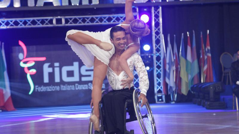 Man in wheelchair holds woman in air while spinning wheelchair.