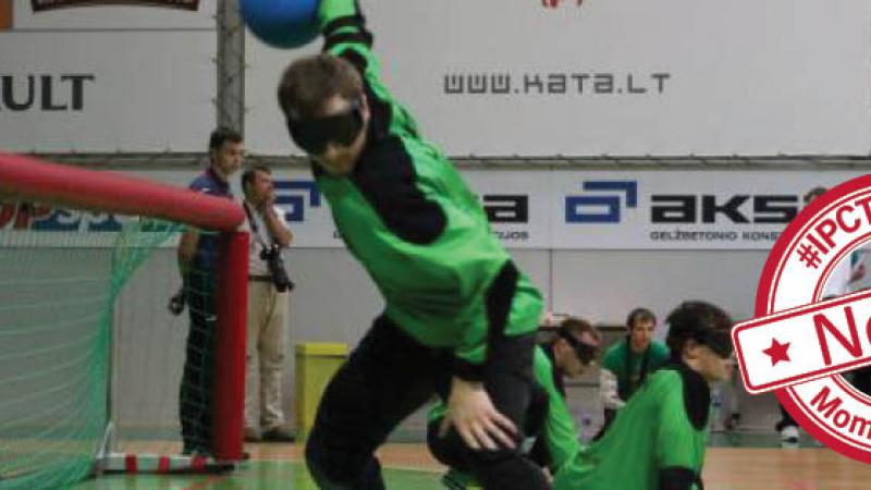 Goalball scene with one player throwing the ball