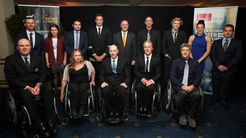 Group picture of people dressed smart, standing and in wheelchairs
