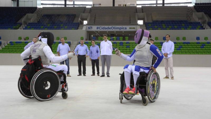 Two wheelchair fencers cross swords in empty arena, some people watching from behind