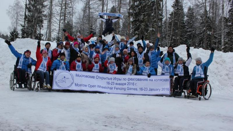 Group picture of people in wheelchairs and standing people in the snow