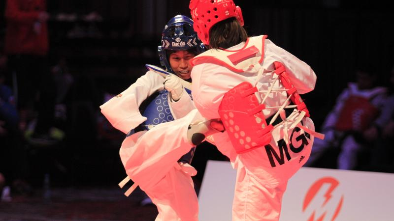A taekwondo athlete kicks her female opponent