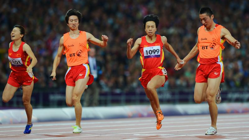 China's Guohua Zhou and her guide Jie Lie cross the line first to win gold ahead of teammates and bronze medalists Daqing Zhou of China and her guide Hui Zhang in the women's 100m T12 Final at the London 2012 Paralympic Games.