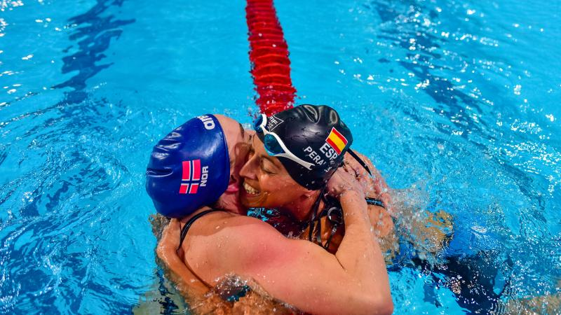 Two swimmers hugging after a race