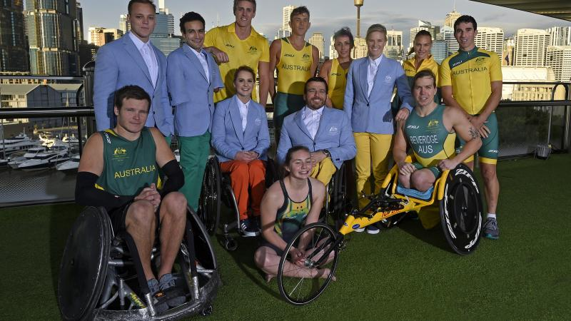 A group of 12 paralympians wearing the new green and yellow uniforms.
