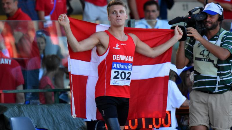 Man in red jersey celebrating with a Danish flag