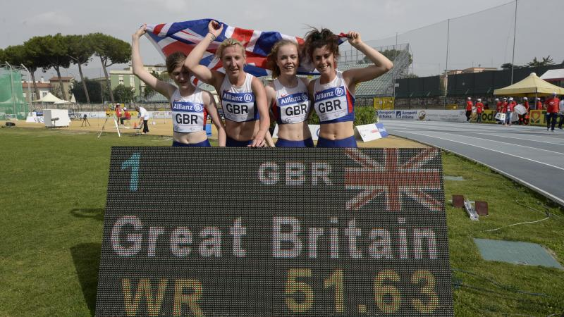 Four girls with British flag post behind a scoreboard