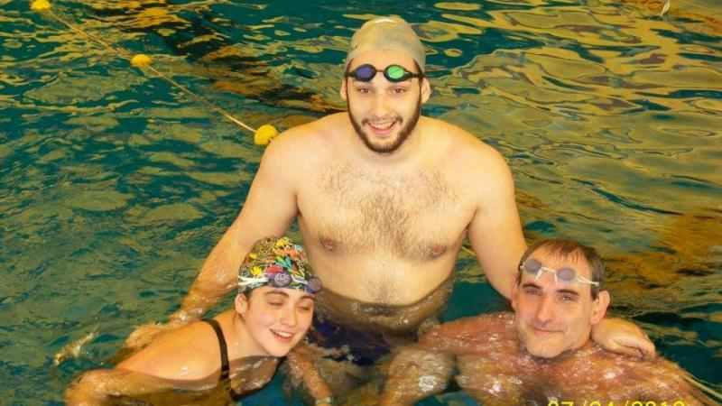 Three people in a pool, smiling to the camera