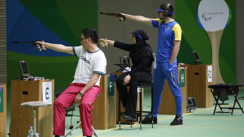 Two sitting and one standing shooting para athlete aiming at the targets