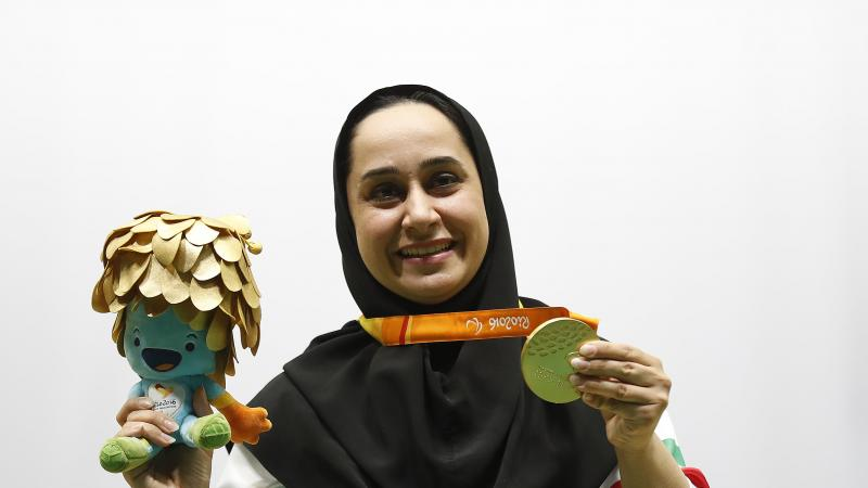 Woman with headscarf poses with medal and mascot in her hand