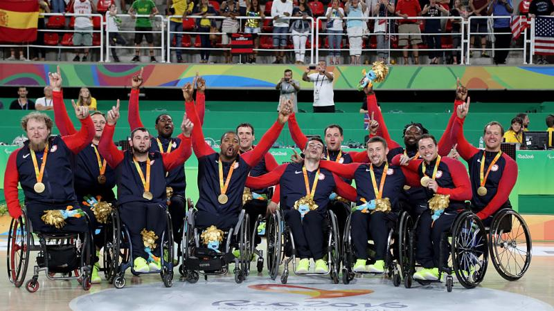 Group of men in wheelchairs celebrate after winning gold.