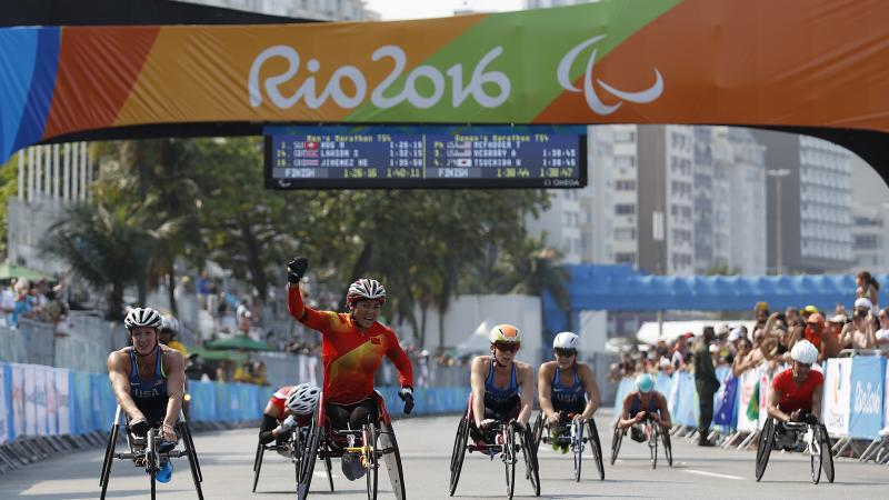 Lihong Zou of China celebrates as she win Gold Medal ahead of Tatyana McFadden USA in Silver Medal position in the Women's T54 Marathon at the Rio 2016 Paralympic Games.