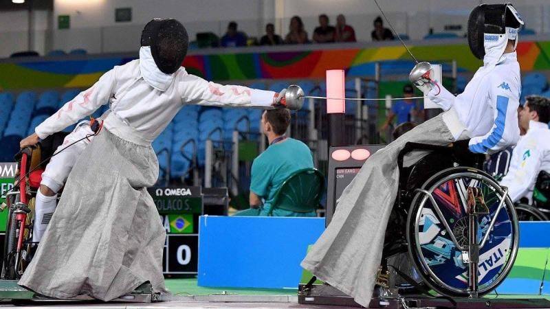 Two men in wheelchairs fencing