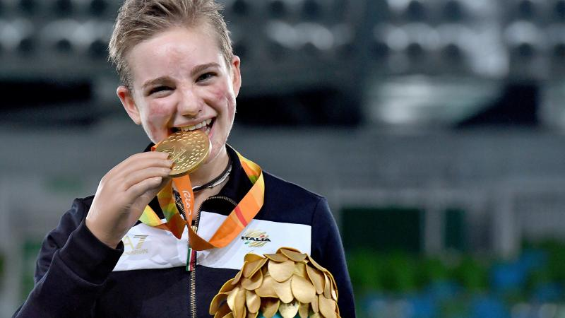 Young woman shows a medal and smiles
