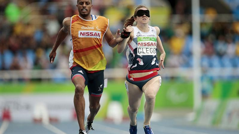 Chris Clarke and Libby Clegg of Great Britain in action during the women's 100m - T11 Semifinals at the Olympic Stadium on Day 2 of the Rio 2016 Paralympic Games
