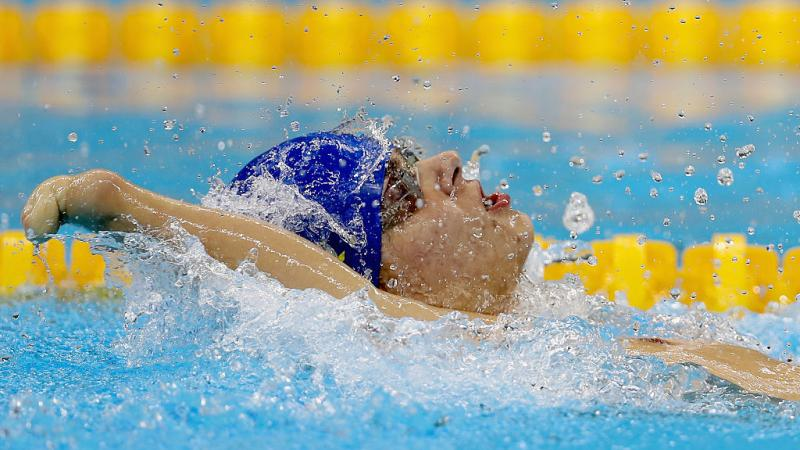 Close up of a swimmer with an impaired arm doing backstroke.