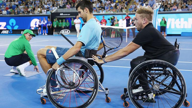 Two men in wheelchairs on a tennis court