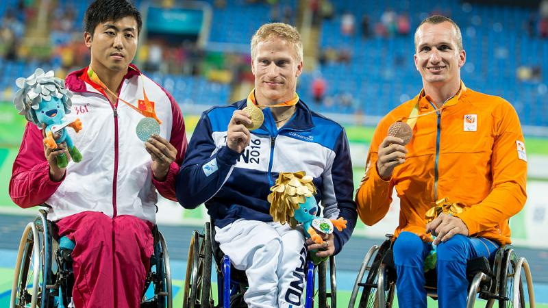 Three men in wheelchairs on a podium showing their medals