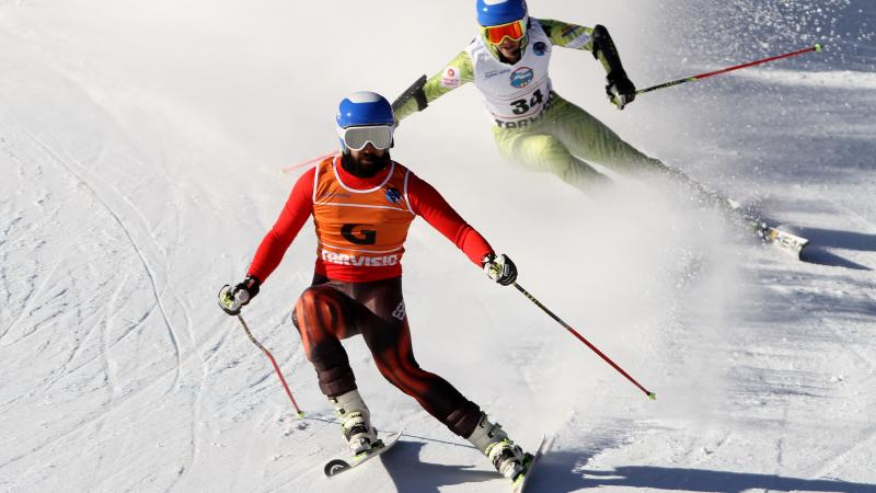 Vision impaired skier and his guide going down a slope
