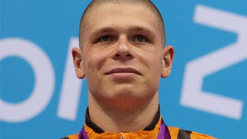 A picture of a man with a gold medal around his neck during a medal ceremony