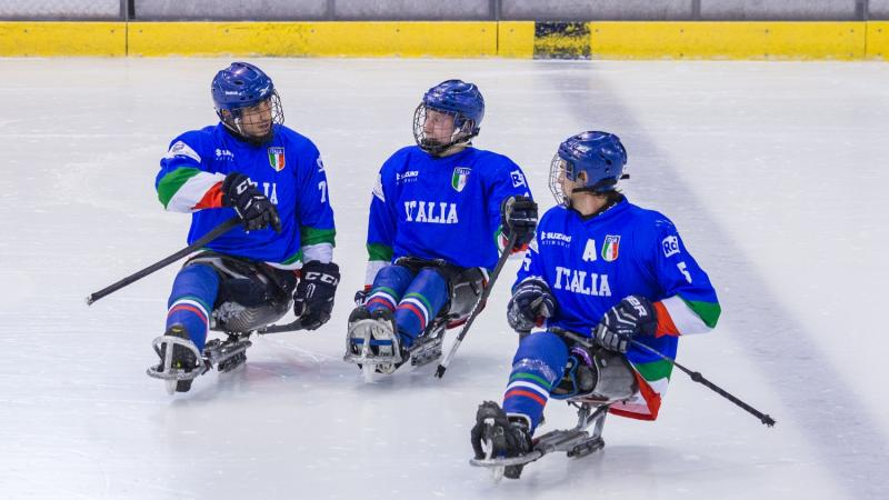 Three Para ice hockey players on ice talking to each other