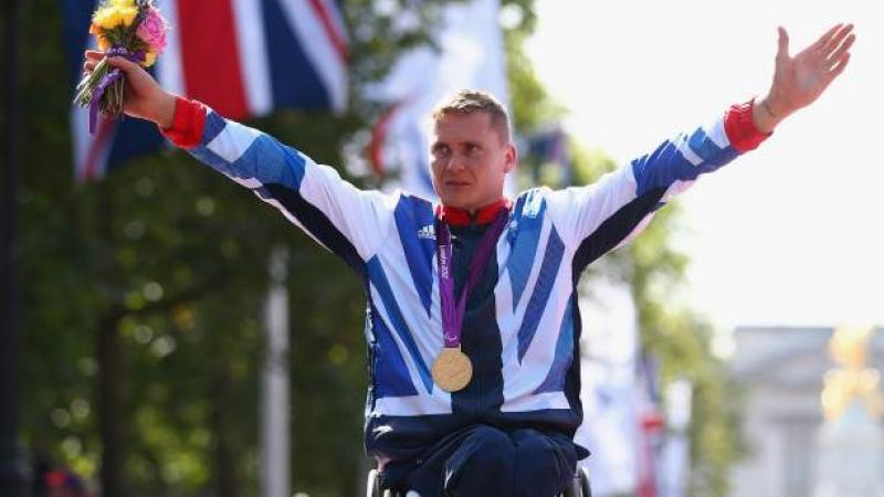 A picture of a man in wheelchair celebrating his victory with a gold medal around his neck